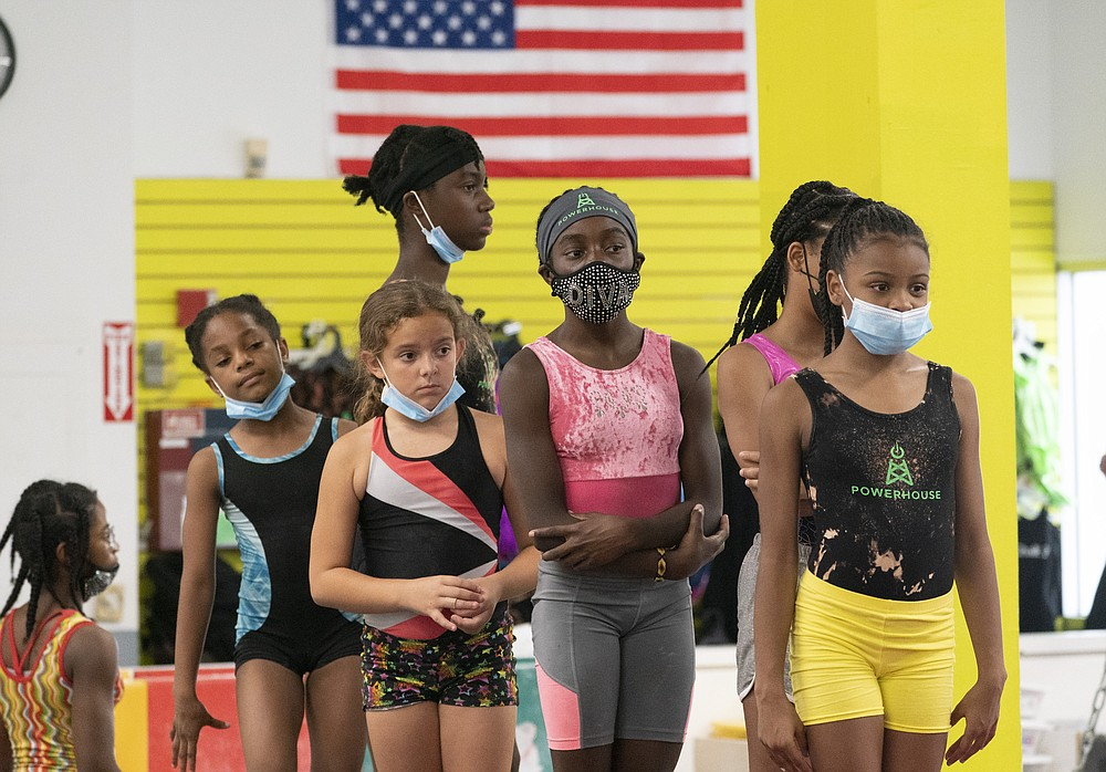Girls wait in line to practice gymnastics, Thursday, July 22, 2021, at Power Moves Gymnastics and Fitness in Cedarhurst, N.Y. The face of gymnastics in the United States is changing. There are more athletes of color starting — and sticking — in a sport long dominated by white athletes at the highest levels. (AP Photo/Mark Lennihan)