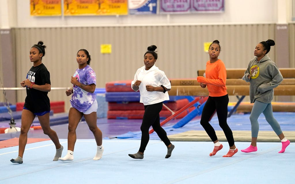 Reigning Olympic champion gymnast Simone Biles, center, trains with fellow gymnasts Tuesday, May 11, 2021, in Spring, Texas.