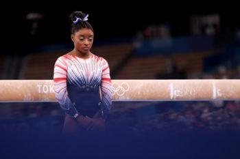 portrait of simone biles standing in front of the balance beam